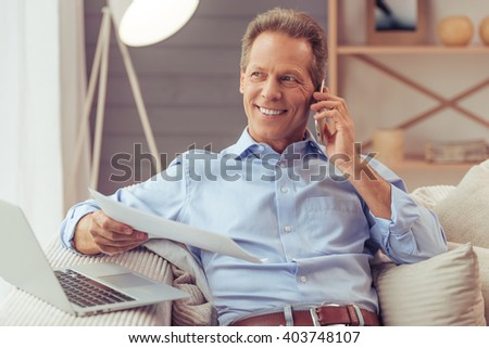 Handsome middle aged businessman is using a laptop, talking on the mobile phone and smiling while working at home - stock photo