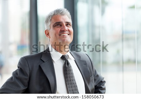 handsome middle aged businessman looking up - stock photo