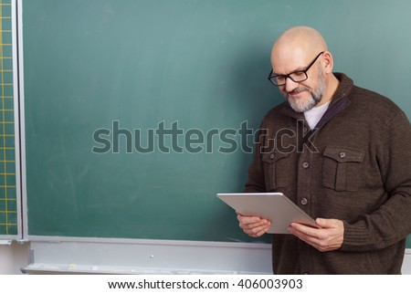 Handsome middle aged instructor in brown shirt and eyeglasses looking at tablet computer in front of green chalkboard - stock photo