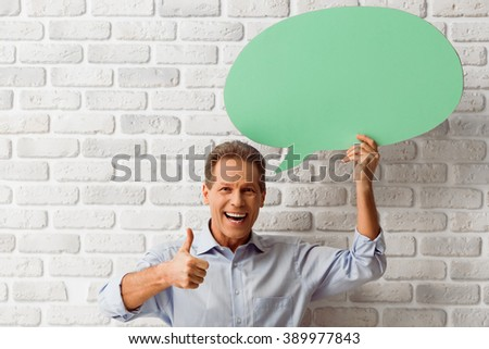 Handsome middle aged man is holding a green speech bubble, showing Ok sign and smiling while standing against white brick wall - stock photo