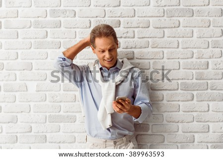 Handsome middle aged man is surprised while using a smart phone, standing against white brick wall - stock photo