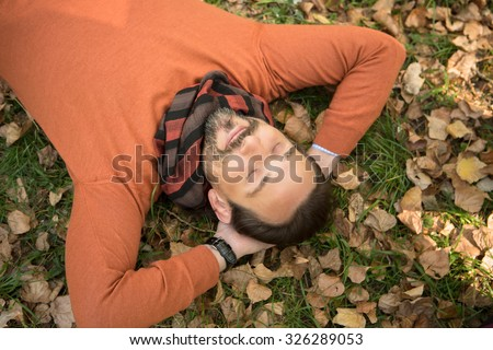 Handsome middle-aged man lying on the autumn leaves and resting from hard-working day in the park. Man in orange sweater lying with closed eyes. - stock photo