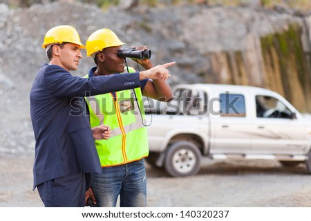 handsome mine manager showing foreman mining site - stock photo
