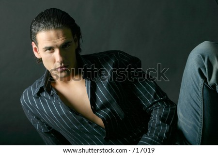 Handsome Model posing in shadows. Black background - stock photo