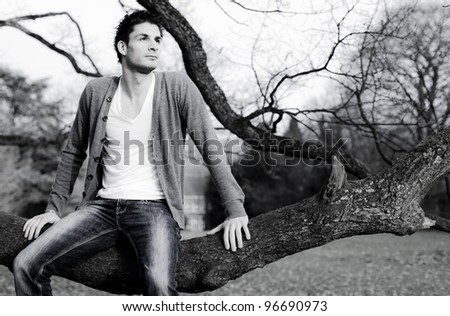 Handsome model sitting on tree branch - stock photo