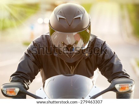 Handsome motorcyclist in black riding his super sport motorcycle. Soft focus. Lens flare - stock photo