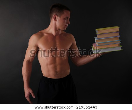 Handsome muscle young man handing books on dark background - stock photo