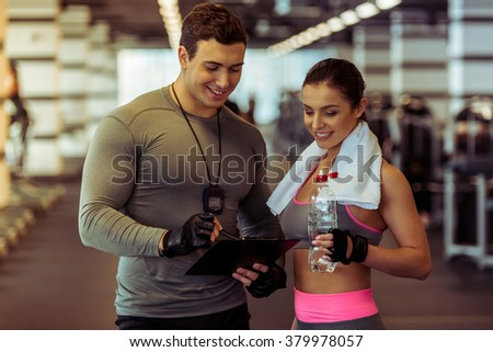Handsome muscled male trainer consulting attractive young female in gym, both smiling - stock photo