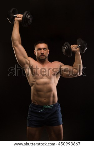 handsome muscular bodybuilder posing on a black background - stock photo