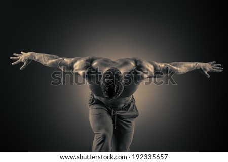 Handsome muscular bodybuilder posing over dark background. Glory of the champion. - stock photo