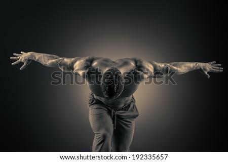 Handsome muscular bodybuilder posing over dark background. Glory of the champion. - stock photo