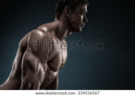 Handsome muscular bodybuilder preparing for fitness training, confidently looking forward. Studio shot on black background. - stock photo