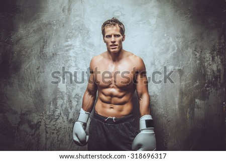 Handsome muscular boxer posing over grey wall. - stock photo
