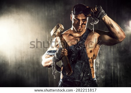Handsome muscular coal miner with a hammer over dark grunge background. Mining industry. Art concept. - stock photo
