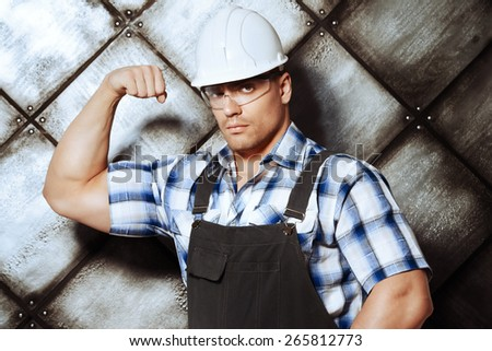 Handsome muscular costruction worker wearing uniform over grunge industrial background. Job, occupation.  - stock photo