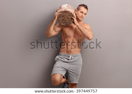 Handsome muscular guy carrying a huge log on his shoulder and looking at the camera - stock photo