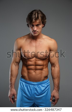 Handsome muscular guy in blue shorts looking down. Isolated on grey background. - stock photo
