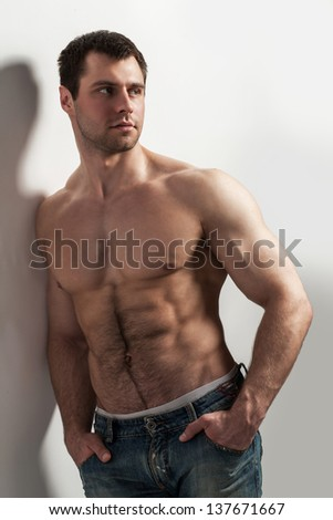 Handsome muscular guy with naked torso isolater over a grey background - stock photo
