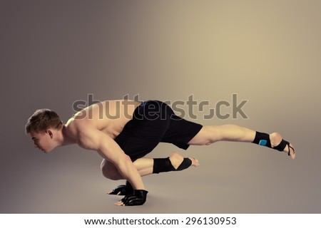 Handsome muscular male athlete performs gymnastic exercise. Sports, acrobatics, gymnastics. - stock photo