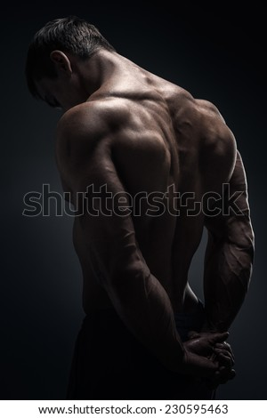 Handsome muscular male bodybuilder posing and turned his back - stock photo