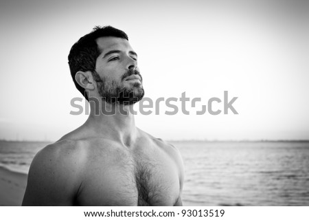 Handsome muscular man deep breathing on the beach. Black and white portrait. - stock photo