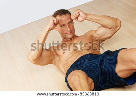 Handsome muscular man doing fitness exerice. - stock photo