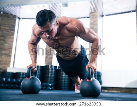 Handsome muscular man doing push ups on kettle ball in crossfit gym - stock photo
