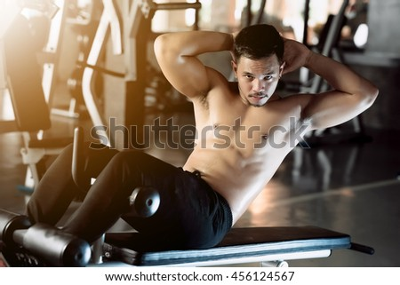 Handsome muscular man doing sit ups in gym club - stock photo