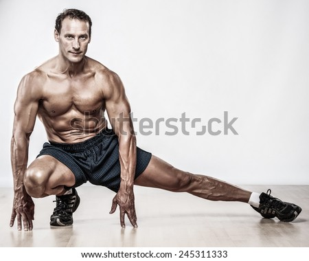 Handsome muscular man doing stretching exercise - stock photo