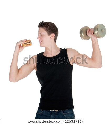 Handsome muscular man eats a hamburger while doing bicep curls. - stock photo