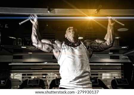 Handsome muscular man in gym making elevations. Bodybuilder training in gym - stock photo