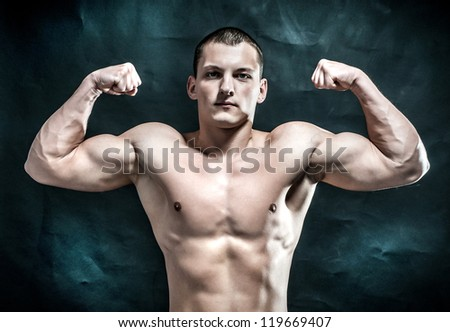 Handsome muscular man on dark background - stock photo
