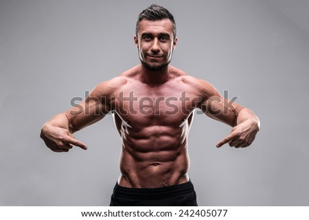 Handsome muscular man pointing at his abs over gray background - stock photo