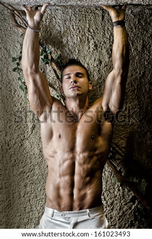 Handsome muscular man shirtless wearing white pants, arms up, in front of concrete wall - stock photo