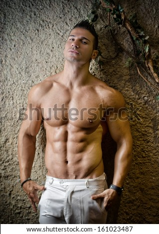 Handsome muscular man shirtless wearing white pants, in front of concrete wall - stock photo
