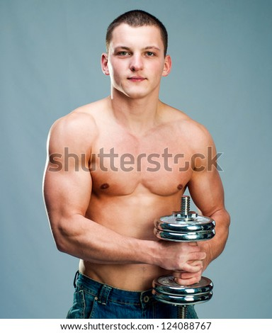 Handsome muscular man use his dumbbell to exercise - stock photo