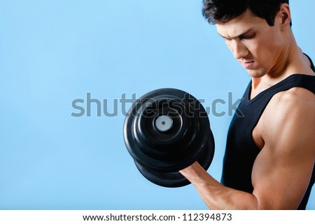 Handsome muscular man uses his dumbbell to exercise flexing bicep muscle - stock photo