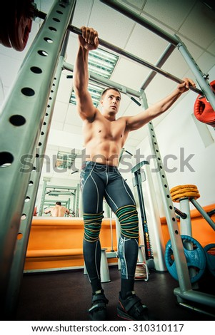Handsome muscular man with weight training equipment in a gym. Sports, bodybuilding. Healthy lifestyle. - stock photo