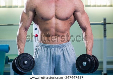 Handsome muscular man working out with dumbbells in gym.Sport, power, dumbbells, tension, exercise - the concept of a healthy lifestyle. Article about fitness and sports. - stock photo