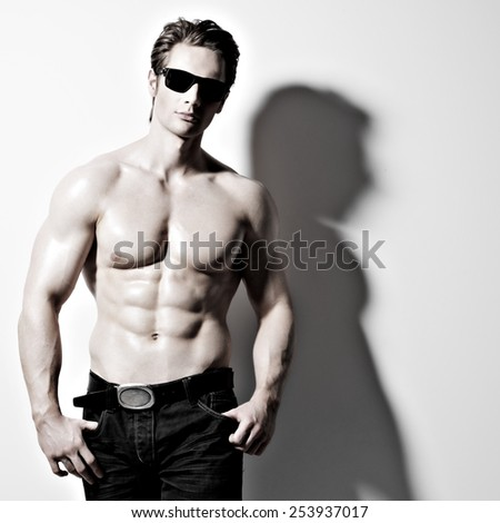 Handsome muscular sexy man in glasses posing at studio as fashion model on a white background with contrast shadows.  - stock photo