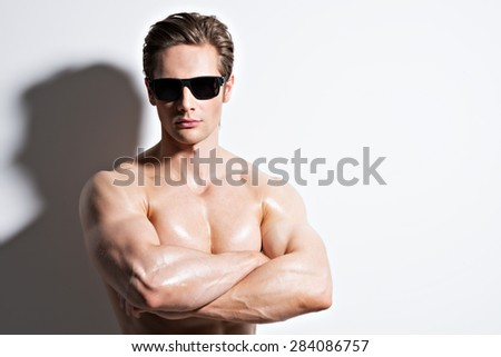 Handsome muscular sexy man in glasses with crossed arms posing at studio as fashion model on a white background with contrast shadows.  - stock photo