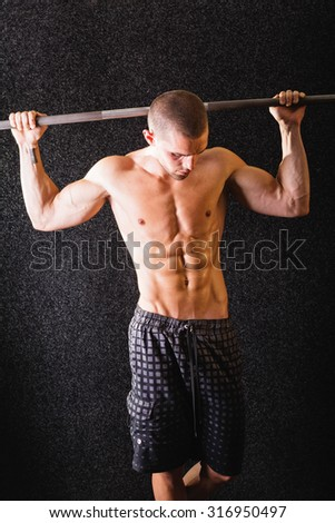 Handsome muscular shirtless Caucasian young man in gym posing looking down. Fit guy with abs lifting weights against black background. Vertical, medium retouch, no filter. - stock photo