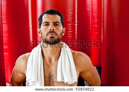 Handsome muscular sports man sweating with a towel on his shoulders looking at camera in front of red punching bags. Fighter. - stock photo