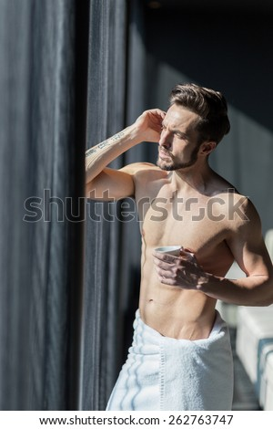 Handsome, muscular, young man drinking his morning coffee in a hotel room standing next to a window and looking against bright sunlight with towel wrapped around his waist - stock photo