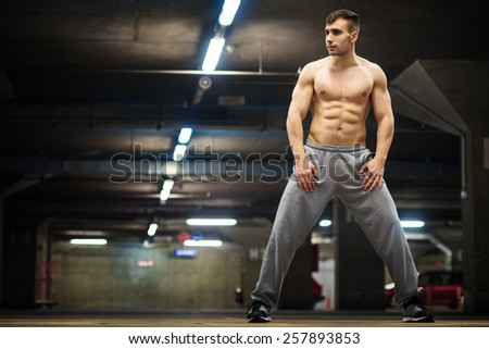 Handsome muscular young man posing at parking garage, natural lights, dark place. - stock photo