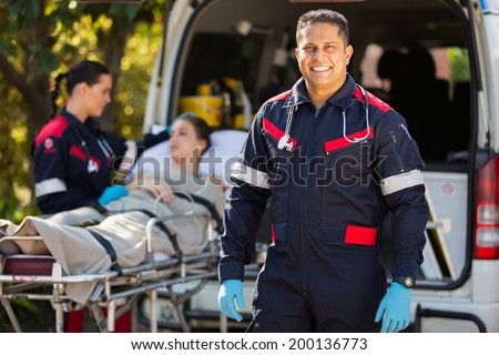 handsome paramedic with colleague and patient on background - stock photo