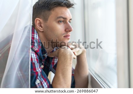 Handsome pensive man guy watching through the window concept sadness sorrow pain waiting. - stock photo
