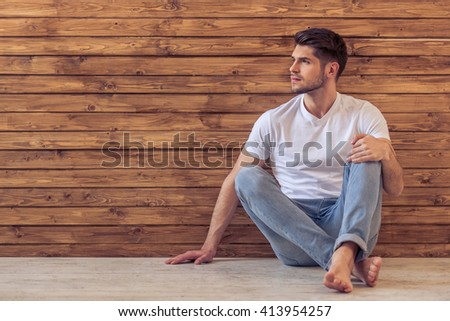 Handsome pensive young man is looking away and thinking, sitting on floor against wooden wall - stock photo