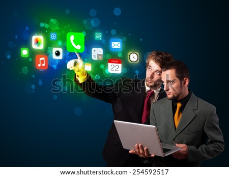 Handsome people pressing colorful mobile app icons with bokeh background  - stock photo