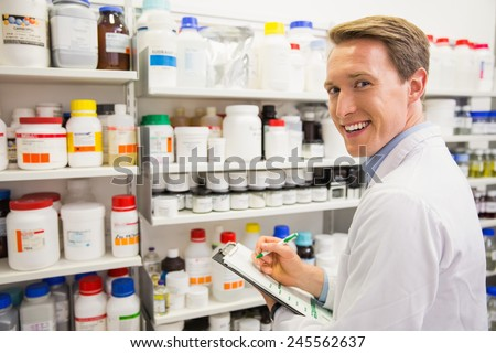 Handsome pharmacist writing on clipboard at the hospital pharmacy - stock photo